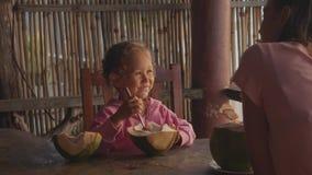 Modern och dottern sitter på seaviewkafét med kokosnötter i ultrarapid arkivfilmer