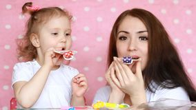Modern och dottern som blåser horn, leende, har gyckel, skrattar och firar lycklig födelsedag deltagare En kvinna och hennes barn lager videofilmer