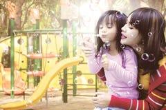 Modern och dottern som blåser såpbubblor på, parkerar royaltyfria bilder