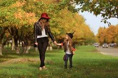 Modern och dottern som går rymma händer på, parkerar royaltyfri fotografi