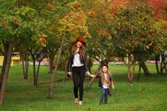 Modern och dottern som går rymma händer på, parkerar Familjlivsstilbegrepp royaltyfria bilder
