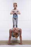 Modern och dottern som gör yoga, övar, kondition, idrottshallen som bär den samma bekväma parade kvinnan p för träningsoverallfam Arkivfoto