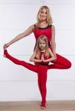 Modern och dottern som gör yoga, övar, kondition, idrottshallsportpai arkivfoto