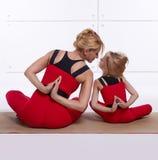 Modern och dottern som gör yoga, övar, kondition, idrottshallsportpai royaltyfria bilder