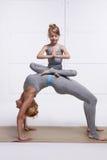 Modern och dottern som gör yoga, övar, konditionidrottshallen som bär samma kvinnaanseende i ställing av brohänder och fot som vi Royaltyfri Fotografi