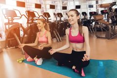 Modern och dottern som gör yoga, poserar på idrottshallen De ser lyckliga, innegrejen och passformen arkivbild