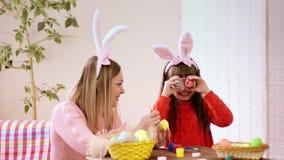 Modern och dottern som maskar på helgdagsaftonen av ägg för påskdagfärg, har gyckel, attraktion och grimasen arkivfilmer