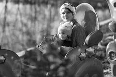 Modern och dottern som rider en karusell, utbildar i parkera royaltyfria bilder