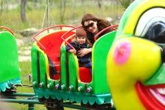 Modern och dottern som rider en larvkarusell, utbildar offentligt parkerar på våren royaltyfri fotografi