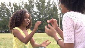 Modern och dottern som spelar applådera leken parkerar in, tillsammans stock video