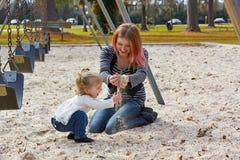 Modern och dottern som spelar med sand parkerar in Arkivfoto