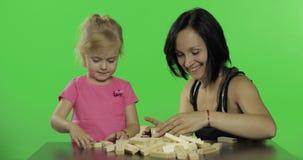 Modern och dottern spelar jengaen Barn som gör ett torn från träkvarter lager videofilmer
