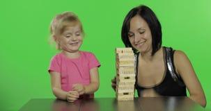 Modern och dottern spelar jengaen Barnet drar träkvarter från torn lager videofilmer