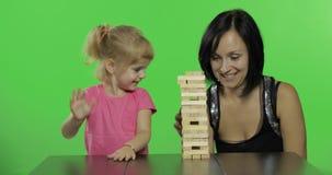Modern och dottern spelar jengaen Barnet drar träkvarter från torn arkivfilmer