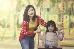 Modern och dottern spelar tillsammans på lekplatsen royaltyfria foton