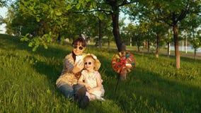 Modern och dottern spenderar lyckligt tid som tillsammans spelar på gräset på solnedgången stock video