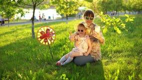 Modern och dottern spenderar lyckligt tid som tillsammans spelar på gräset på solnedgången arkivfilmer