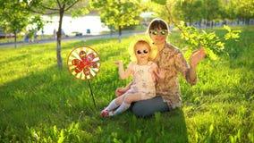 Modern och dottern spenderar lyckligt tid som tillsammans spelar på gräset på solnedgången lager videofilmer