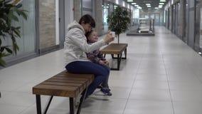 Modern och dottern tar selfies på en smartphone i en galleria eller ett kontor lager videofilmer