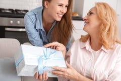 Modern och dottern tillsammans tillbringar veckoslutet hemma dottern som ger gåvan till mamman royaltyfri fotografi