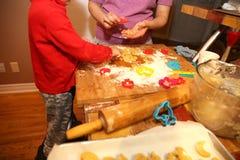 Modern och hennes behandla som ett barn lite göra handkakor hemma i köket arkivfoto