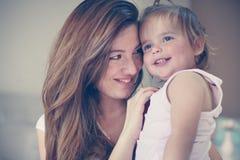Modern och hennes gulligt behandla som ett barn hemma Modern som rymmer behandla som ett barn lite, in Arkivfoto