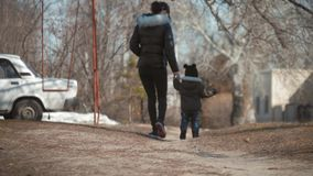 Modern och hennes lilla son går på rymma händer, begrepp av moderskap och barndom arkivfilmer