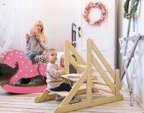 Modern och hennes småbarn är i en barnkammare royaltyfri fotografi