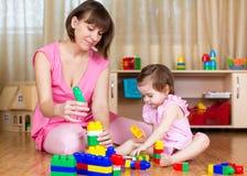 Modern och hennes unge spelar med kvarterleksaker hemma Arkivfoton