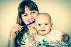 Modern och hon behandla som ett barn borsta retro stil för tänder tillsammans - arkivbilder