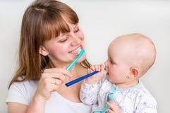 Modern och hon behandla som ett barn borsta tänder tillsammans royaltyfri bild