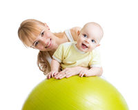 Modern och hon behandla som ett barn ha gyckel med den gymnastiska bollen Royaltyfri Bild