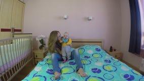 Modern och 5 månad den gamla dottern behandla som ett barn skratt och spelar på säng 4K arkivfilmer