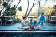 Modern och 3 söner spelar leksaker arkivfoton