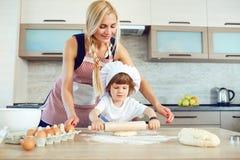 Modern och sonen bakar kakor i köket arkivbild