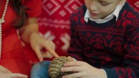 Modern och sonen betraktar en julgrankotte Julgåva nära julgranen hemma lager videofilmer
