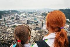 Modern och sonen beundrar en stad med ett observationsdäck av Hohensalzburg ?sterrike salzburg Familjsight arkivfoto