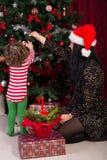 Modern och sonen dekorerar julgranen Fotografering för Bildbyråer