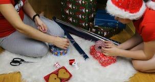 Modern och sonen förbereder julklappar för jul arkivfilmer