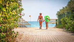 Modern och sonen går till havsstranden Semesterortsemester på den tropiska stranden strandbana till Arkivfoto