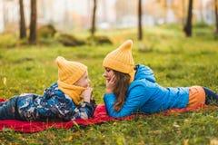 Modern och sonen i gula hattar ligger på gräset royaltyfri foto