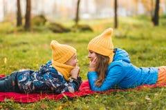 Modern och sonen i gula hattar ligger på gräset royaltyfri bild