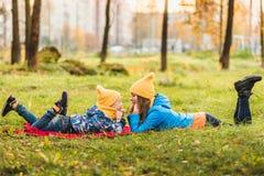 Modern och sonen i gula hattar ligger på gräset royaltyfria bilder