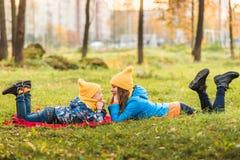 Modern och sonen i gula hattar ligger på gräset arkivbilder