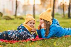 Modern och sonen i gula hattar ligger på gräset arkivfoton