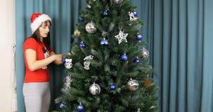 Modern och sonen i julkläder dekorerar julgranen hemma lager videofilmer