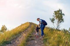 Modern och sonen klättrar upp kullen Arkivfoton