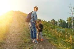 Modern och sonen klättrar upp kullen Royaltyfri Bild