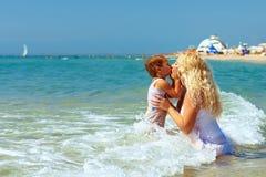 Modern och sonen kysser i havsvatten på strand Arkivbild