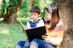 Modern och sonen läste en bok tillsammans Royaltyfri Bild